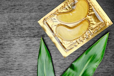 Golden cosmetics hydrogel patches and green leaves on a black wooden background with copy space. Skin care and cosmetology concept. Lifting anti-wrinkle collagen mask. Standard-Bild