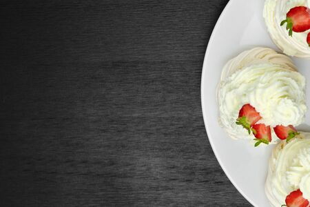 Top view of meringue cakes with cream and halves of strawberries on the plate on a black wooden background with copy space. Delicious dessert
