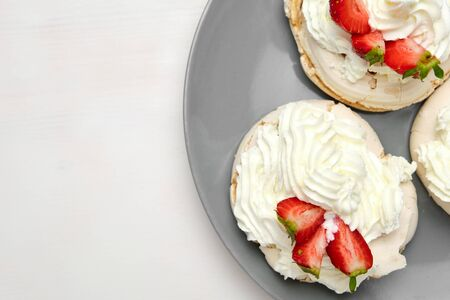Meringue cakes with strawberry and whipped cream on a grey plate on a green background with copy space. Homemade confectionery.