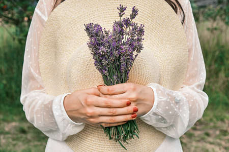 Female holding a hat and bouquet of lavender in her hand. Provence rural stye Stock Photo