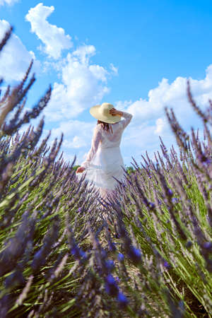 Beautiful young woman in a white wedding dress and hat standing in the lavender field.