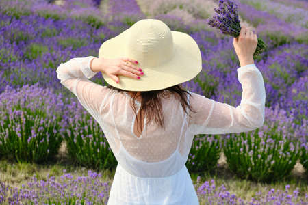 Young woman in a white dress raised her hands with bouquet of lavender above a head in a background of purple field.