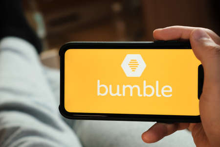 Bumble application on the smartphone in mans hand. Man laying and using application for dating and meeting. Social network concept, July 2020, Prague, Czech Republic