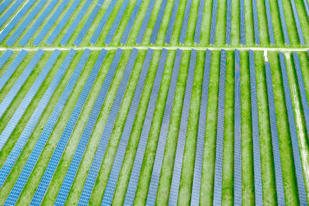 Top view of solar power station for production of electricity. Vertical straight lines of solar panels in the green field. Renewable eco friendly energy source 免版税图像