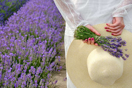 Young woman in a white light dress holding behind her back a hat and a bouquet of lavender in a purple filed in blossom with copy space.
