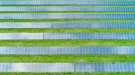 Equal lines of solar panels in the green field. Top view of solar power station for generation green energy.