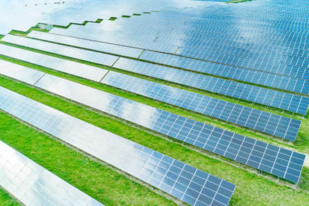 Solar power station in the green field. Blue sky and clouds are reflected on the photovoltaic panel. Production of solar energy