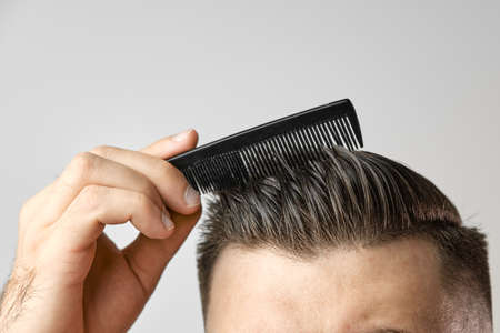 Close up young man brushing his hair with a plastic comb. Styling hair after barbershop. Hair healthcare. Lost of hair concept