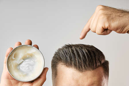 Man applying a clay, pomade, wax, gel or mousse from round metal box for styling his hair after barbershop hair cut. Advertising concept of mans products. Treatment and care against lost of hair Banque d'images
