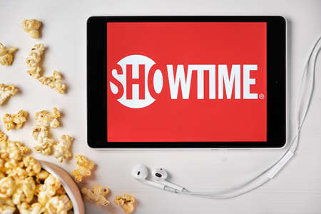 Showtime logo on the tablet screen laying on the white table with scattered popcorn and Apple earphones. Spending free time at home or news advertisement, September 2020, San Francisco, USA.