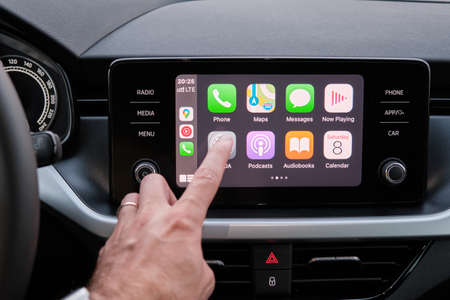 Close up mans hand touching an icon in the Apple Carplay on car dashboard screen, September 2020, San Francisco, USA