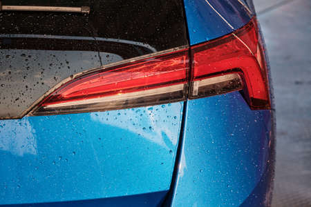 Close up a taillight of a blue car in the drops of water after rain of car washing.