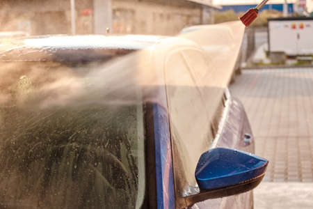 Car washing under high pressure water at sunset. Manual car cleaning system outdoor. Self service car washing concept.