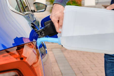 Close up man filling a diesel engine fluid from canister into the tank of blue car. Diesel exhaust fluid for reduction of air pollution. Environmental friendly and eco solution.