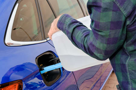 Man filling a diesel engine fluid from canister into the tank of blue car. Diesel exhaust fluid for reduction of air pollution.