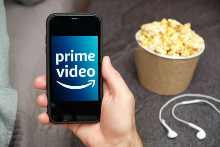 Close up mans hand holding a mobile phone with Prime Video Amazon logo with Apple earphones and popcorn box next to him, August 2020, San Francisco, USA
