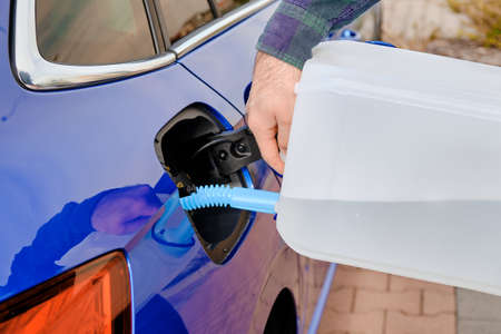 Close up man filling a diesel engine fluid from canister into the tank of blue car. Diesel exhaust fluid for reduction of air pollution. Environmental friendly and eco solution. Banque d'images
