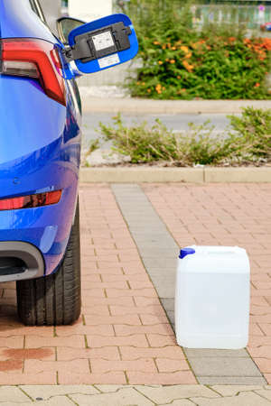 A white canister with a diesel exhaust fluid DEF for reduction of air pollution standing near a blue car.