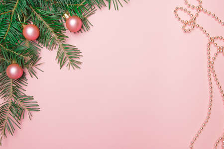 Christmas pink background with fir branch, pink balls and beads in the corner with copy space.