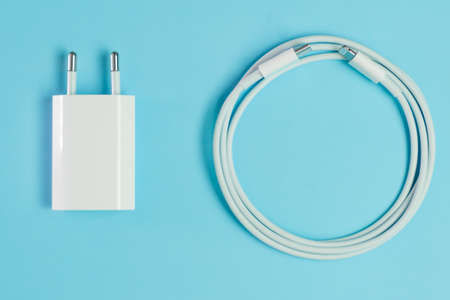 A white smart phone charger cable with lightning hi speed USB A connector and adapter.