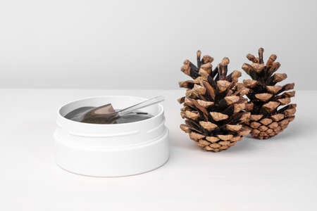 A white box with golden eye patches on the white table with pine cones. Cosmetics product for skin care
