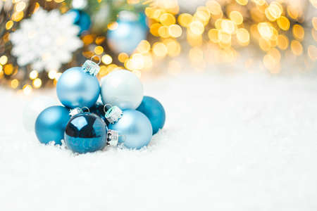 Blue Christmas balls laying on the snow on the background of Christmas tree and blurred golden lights with copy space. Preparation for New Year party. Stockfoto