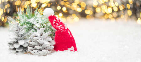 Pine cones, Santa Claus hat, pine branch on the snow with golden blurred lights on the background. Winter decoration with copy space.