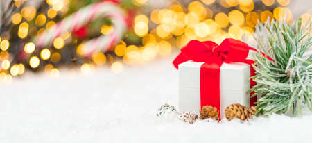 Christmas gift or present with red ribbon, small spruce or pine cones, pine branch on the background of blurred lights of garland.