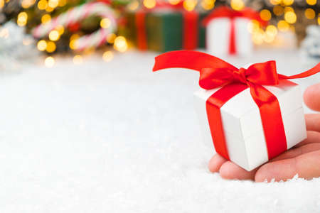 Close up woman hand holding a white gift box with a red ribbon on the background of presents, candy stick, Christmas tree and golden lights with copy space 版權商用圖片