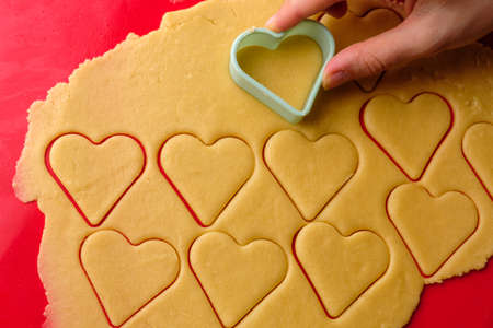 Making gingerbread cookies in heart shape using plastic cutter on the red silicon baking mat. Sweets for St. Valentines Day.