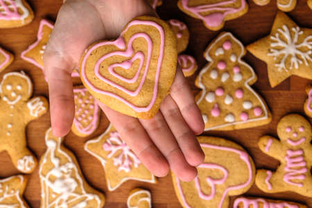 Cookies for Valentines Day in woman hands in the background of gingerbread.