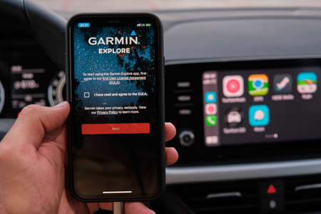 Garmin explore logo on the screen of smart phone in mans hand on the background of car dashboard screen with application of navigation or maps. January 2021, Prague, Czech Republic. Editorial