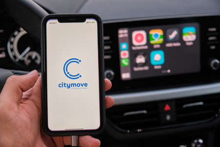 Citymove on the screen of smart phone in mans hand on the background of car dashboard screen with application of navigation or maps. January 2021, Prague, Czech Republic. Editorial