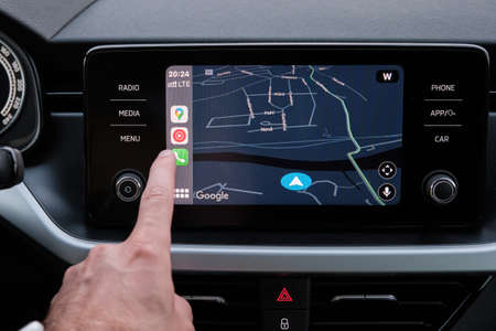 Close up mans hand select the application of navigation or maps on the car dashboard. January 2021, Prague, Czech Republic.