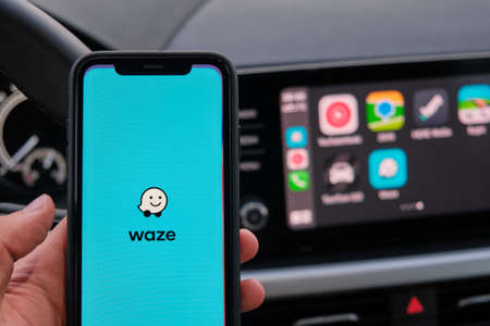 Waze on the screen of smart phone in mans hand on the background of car dashboard screen with application of navigation or maps. January 2021, Prague, Czech Republic.