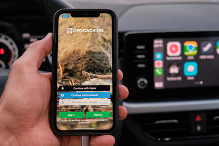 Welcome to BMW Motorrad connected on the screen of smart phone in mans hand on the background of car dashboard screen with application of navigation or maps. January 2021, Prague, Czech Republic. Editorial