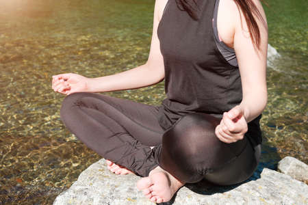 Woman practising yoga or meditating in sportswear on the stone near the lake at sunlight.