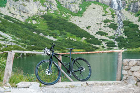 Sport bike and helmet standing near the lake in the mountains. Turisme in High Tatars. September 2020, Velicka Valley, Slovak Republic. Editorial