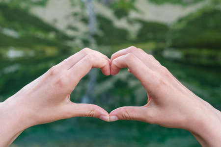 Womans making heart shape with her hands against the mountains near to the lake.
