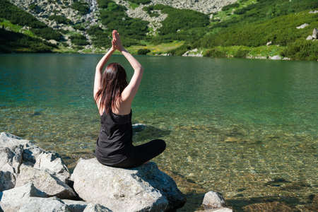 Young sporty woman practicing yoga in black sportswear near the river or lake with transparent water