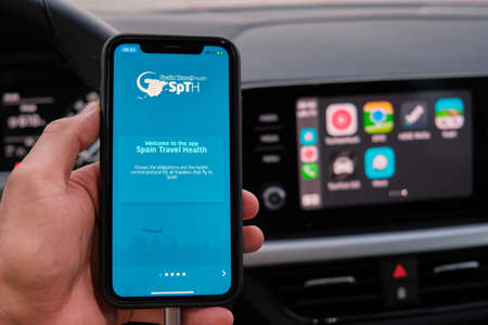 Spain Travel Health app on the screen of iphone in mans hand on the background of car dashboard screen with application of navigation or maps from Apple Carplay. January 2021, Prague, Czech Republic Editorial