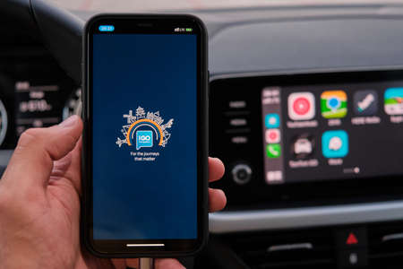 IGO logo on the screen of smart phone in mans hand on the background of car dashboard screen with application of navigation or maps. January 2021, Prague, Czech Republic.
