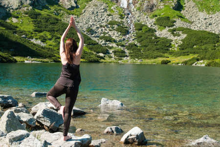 Woman practicing balancing yoga near the lake in the mountains. Young girl standing on the one leg on the stone in the black sportwear.