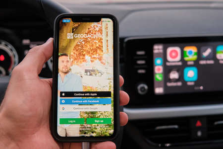 Geocaching maps on the screen of smart phone in mans hand on the background of car dashboard screen with application of navigation or maps. January 2021, Prague, Czech Republic.