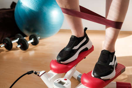 Close woman legs doing cardio on the stepper and using elastic bands with ball, and dumbbells on the background. Workout at home.