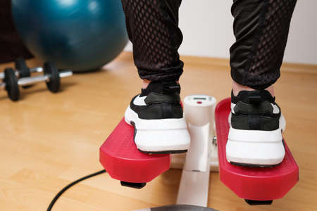 Back view on the woman feet in sneakers doing exercising on the twist stepper or stair stepper machine at home during lockdown. Keep fit. Cardio at home. Standard-Bild