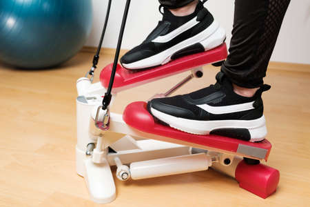 Close up womans feet in sneakers training on the twist stepper with digital display and gum expanders at home during lockdown.