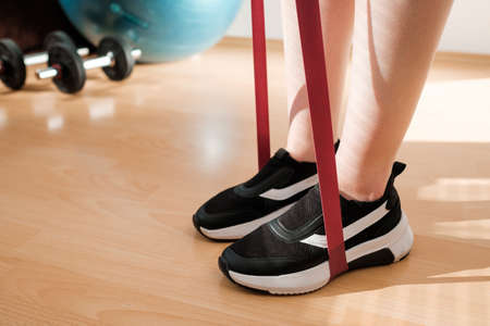 Close up female legs in sneakers doing exercises with fitness elastic bands at home during lockdown. Home workout. with resistances bands. Standard-Bild