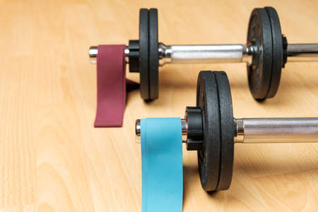 Dumbbells and elastic bands on the floor at home. Keeping fit during lockdown. Fitness equipment for strength training