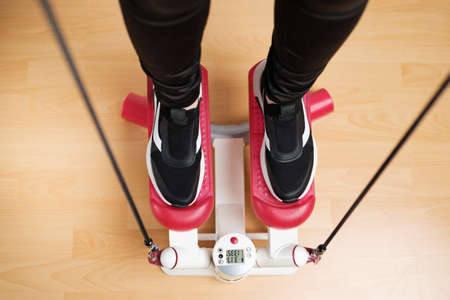 Top view on woman legs doing exercising on the twist stepper with digital display and gum expander. Workout at home.